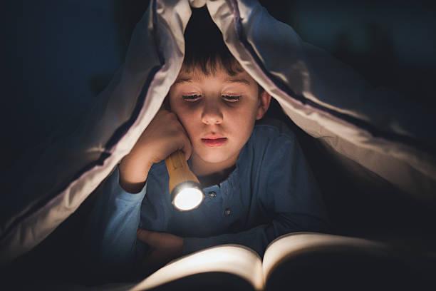 little boy reading a book under the covers with flashlight - deckenleuchte kinderzimmer stock-fotos und bilder