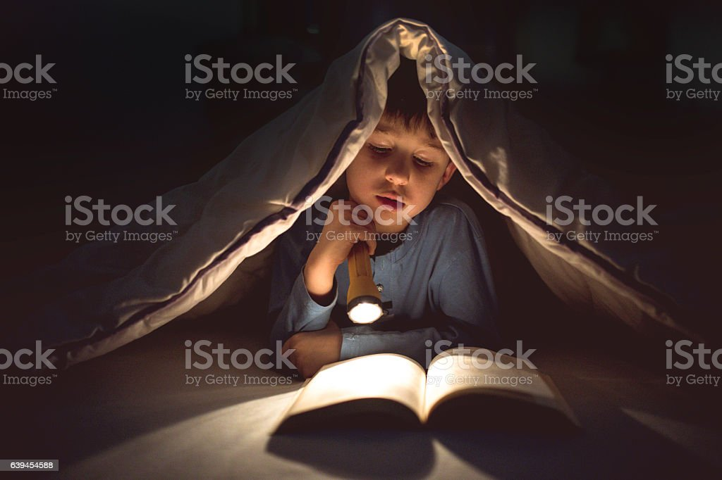 Little boy reading a book under the covers with flashlight - foto de acervo