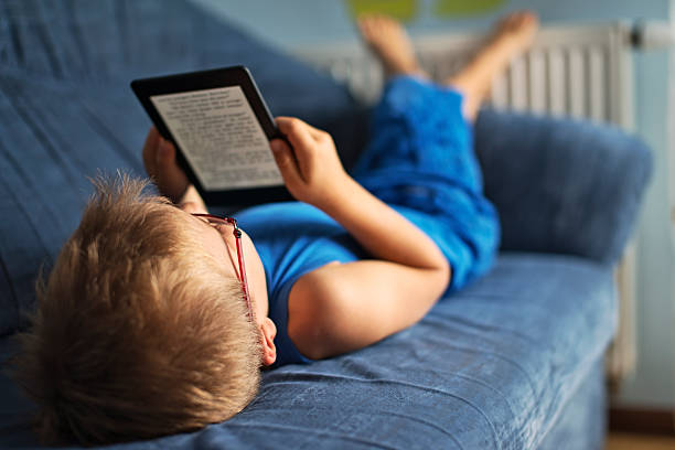 Little boy reading an ebook on couch stock photo