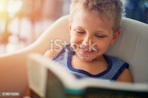 istock Little boy reading funny book 578570030