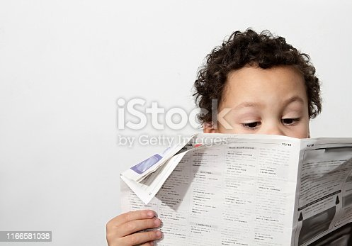 Little boy reading newspaper and smiling in the morning been educated with white background stock photo