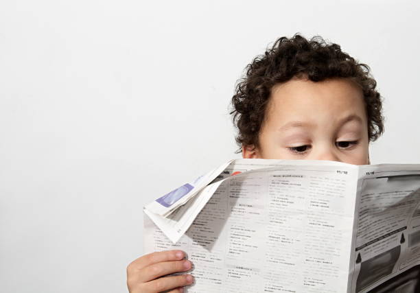 Little boy reading newspaper stock photo Little boy reading newspaper and smiling in the morning been educated with white background stock photo newsletter stock pictures, royalty-free photos & images