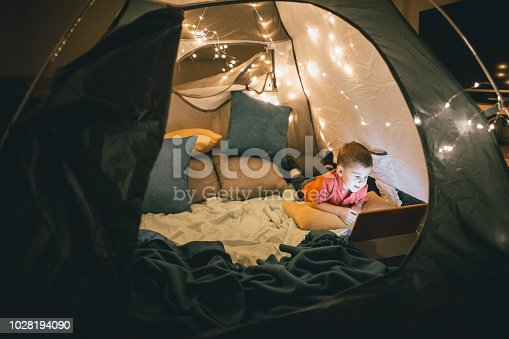 Little boy watching something on the digital tablet in the tent at bedroom