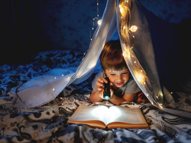 Little boy reads with pocket light. Toddler plays in tent made of linen sheet on bed. Cozy evening with favorite book. stock photo