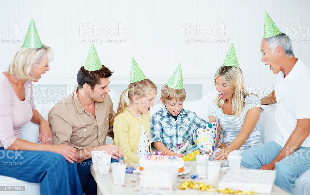 Little boy receiving birthday gifts from his family royalty-free stock photo