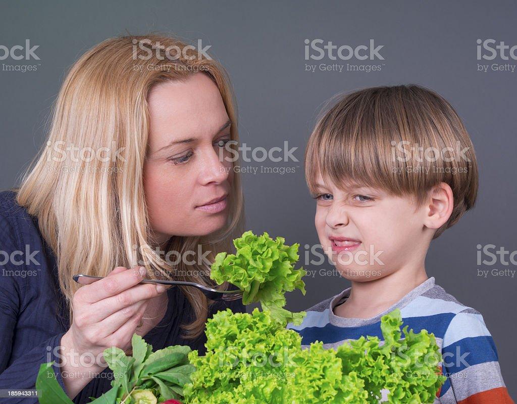 Little boy refusing to eat green salad stock photo