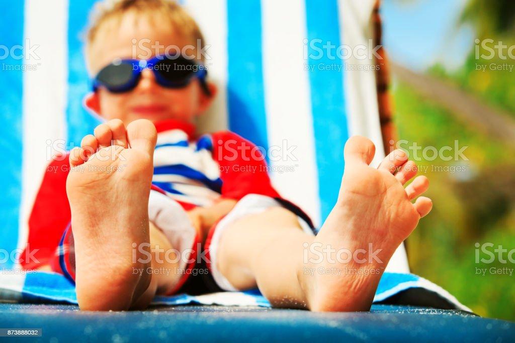 little boy relax on tropical beach, focus on feet - foto stock