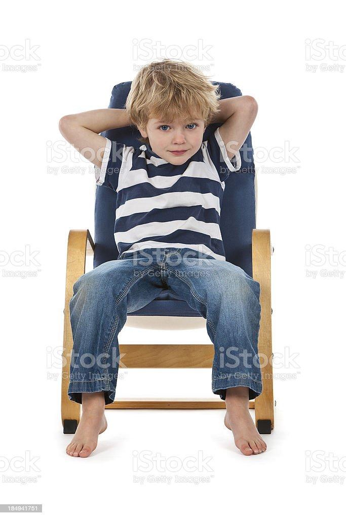 Little Boy Relaxing In Chair stock photo