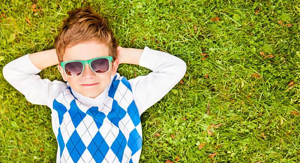 kleine junge entspannend auf gras - sonnenbrille kleinkind stock-fotos und bilder