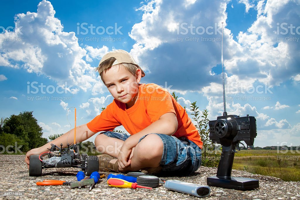 Little boy repaire the radio control car outdoor near field stock photo
