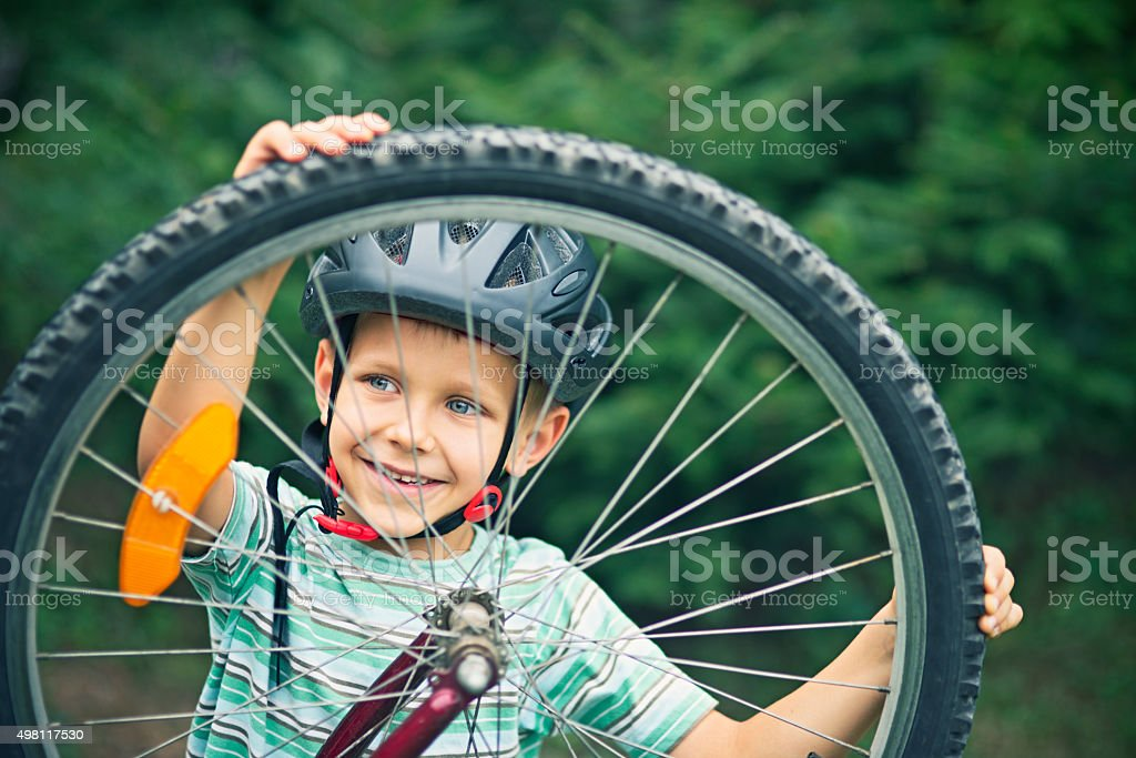Little boy repairing a bicycle stock photo