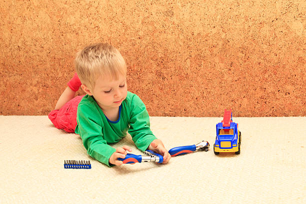reparatur kleiner junge mit kunststoff-spielzeugauto, das early learning-konzept - kindergarten handwerk stock-fotos und bilder