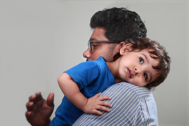 A little boy rests on his father's shoulder stock photo
