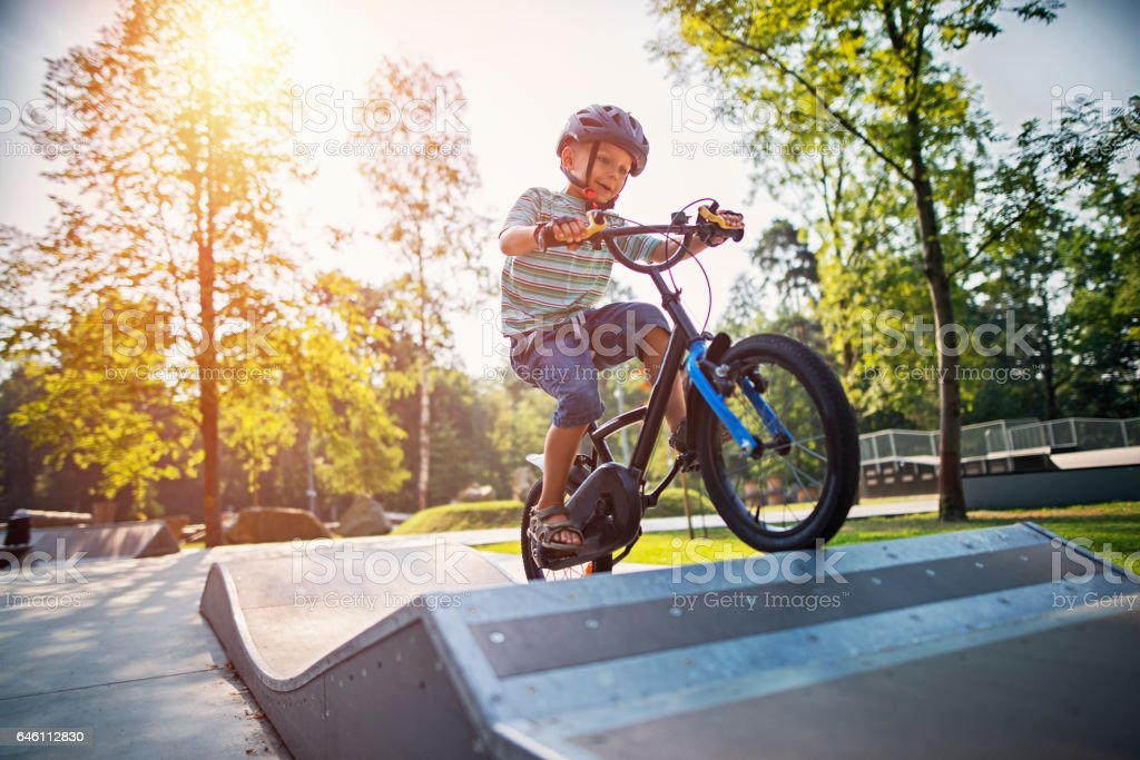 Little boy riding a bicycle on ramp stock photo