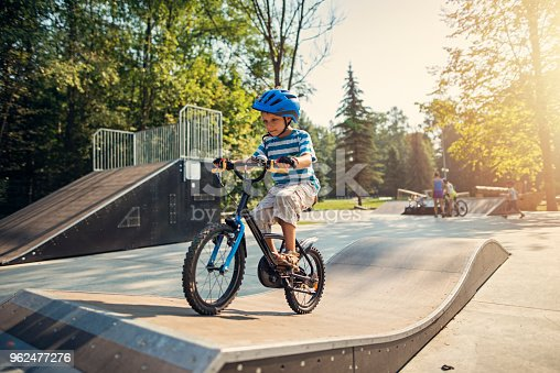 Little boy wearing a helmet is riding a bicycle on ramp in city park on summer day. The boy is aged 6 and is smiling. Nikon D800