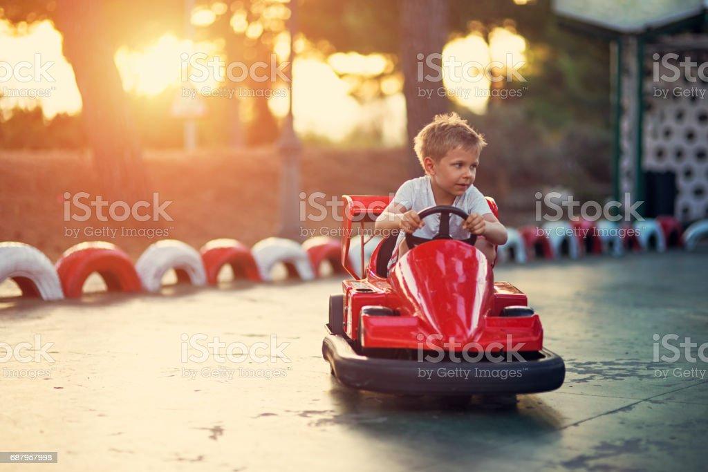 Niño montando un coche de parachoques de Parque de atracciones - foto de stock