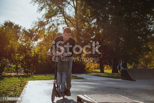 665192886 istock photo Little boy riding a push scooter with his dad 1176555480