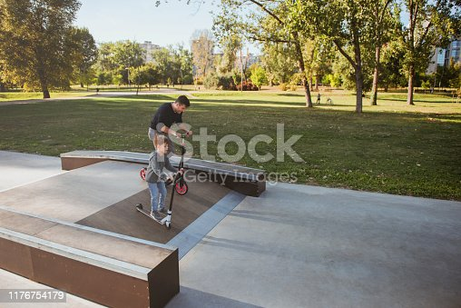 665192886 istock photo Little boy riding a push scooter with his dad 1176754179