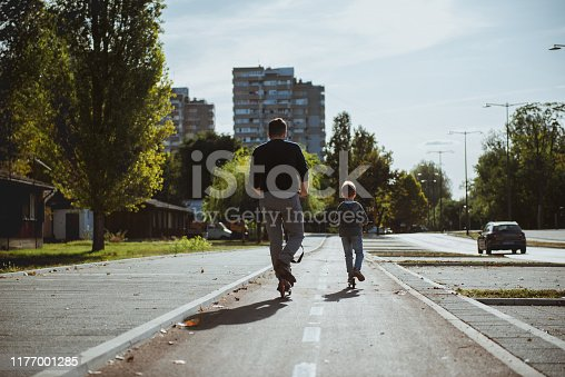 665192886 istock photo Little boy riding a push scooter with his dad 1177001285