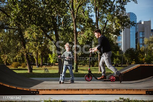665192886 istock photo Little boy riding a push scooter with his dad 1177001342