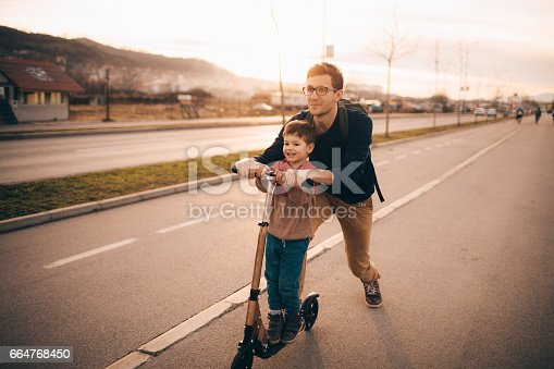 665192886 istock photo Little boy riding a push scooter with his dad 664768450