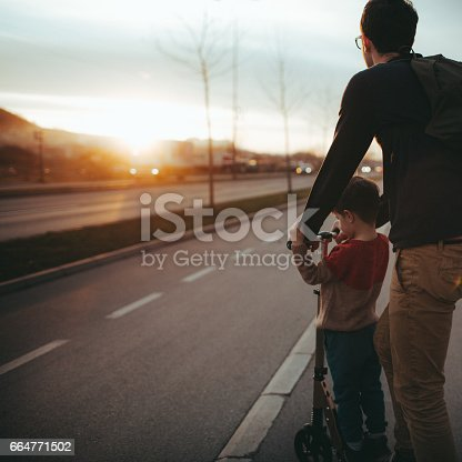 665192886 istock photo Little boy riding a push scooter with his dad 664771502
