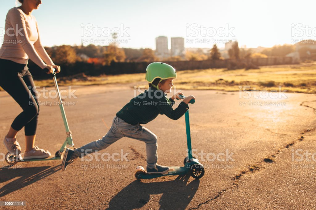 Little boy riding a push scooter with his mom stock photo