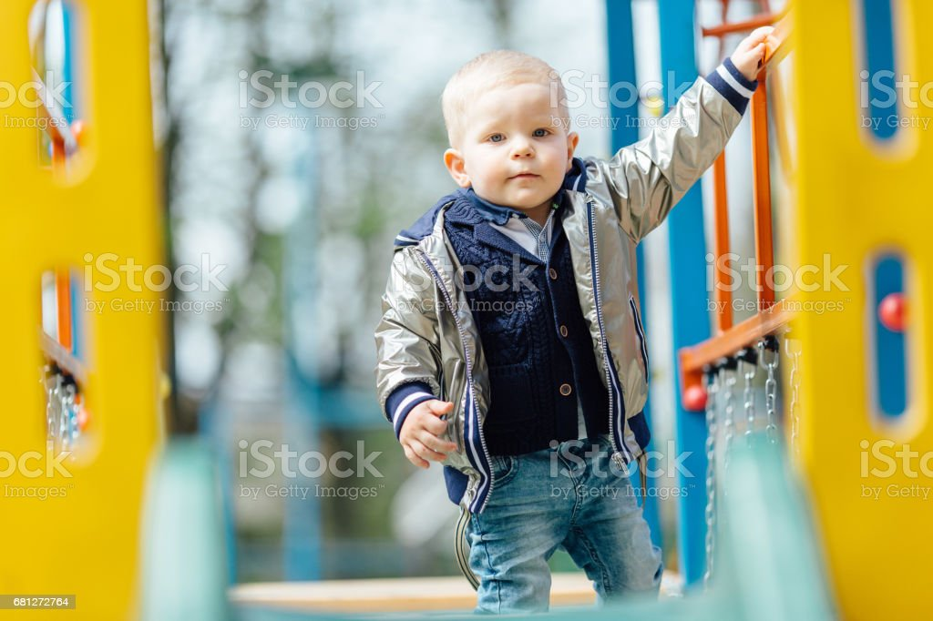 Little boy riding a swing in park playground royalty-free stock photo