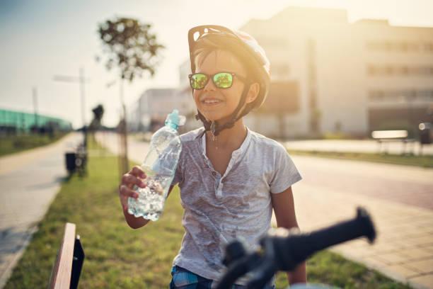 Kleiner Junge, Reiten, Fahrrad- und Trinkwasser – Foto