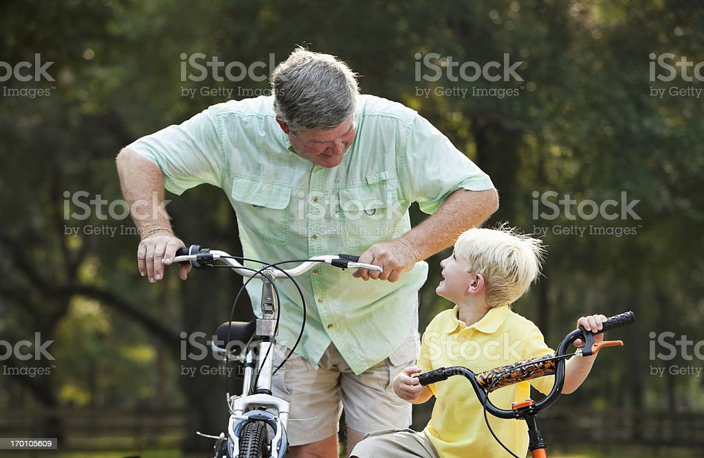 Little boy riding bike with grandfather royalty-free stock photo