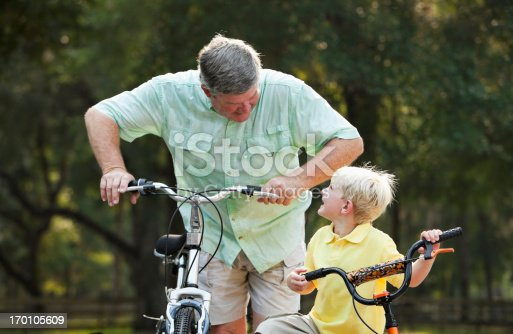 853720192 istock photo Little boy riding bike with grandfather 170105609