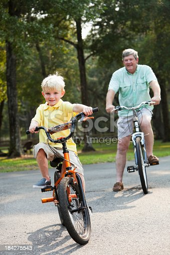 853720192 istock photo Little boy riding bike with grandfather 184275543
