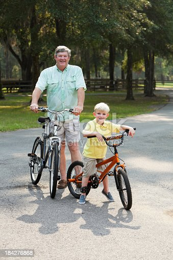 853720192 istock photo Little boy riding bike with grandfather 184276868