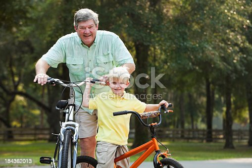 853720192 istock photo Little boy riding bike with grandfather 184362013