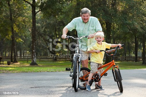 853720192 istock photo Little boy riding bike with grandfather 184847829