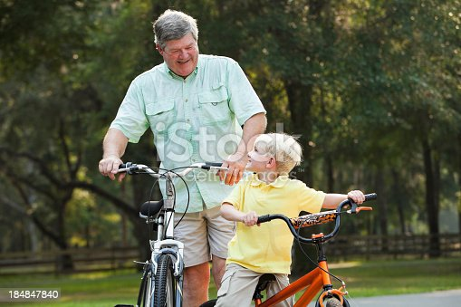 853720192 istock photo Little boy riding bike with grandfather 184847840