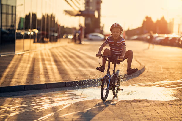 Little boy riding his bike through a puddle stock photo