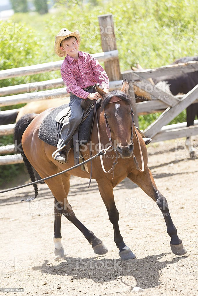 Little boy riding horse in corral at family ranch royalty-free stock photo