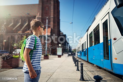 Little boy waiting for a tram on a tram stop. The boy is looking at the approaching train and is getting ready to get on it on his way to school. Nikon D850