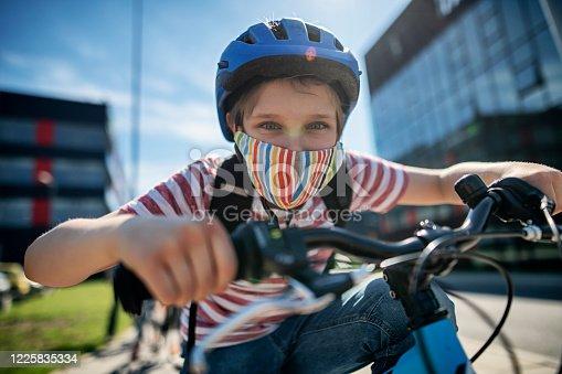 Little boy riding his bike to school during COVID-19 pandemic. Nikon D850