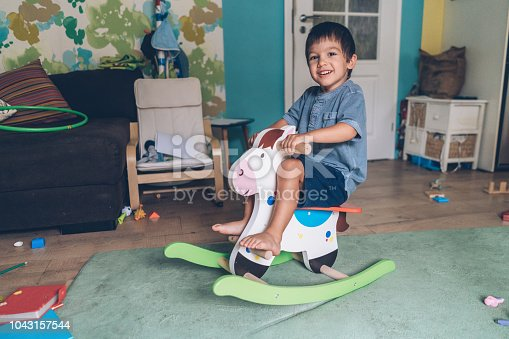 Little boy riding wooden rocking horse at home