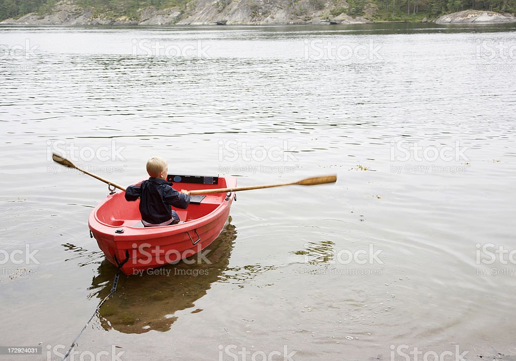 Little boy rowing small red boat on the calm sea. royalty-free stock photo