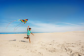 Cute boy run on the sand beach near the sea holding colorful rainbow stripped kite