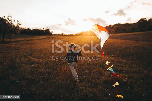 istock Little boy running a kite 672823668