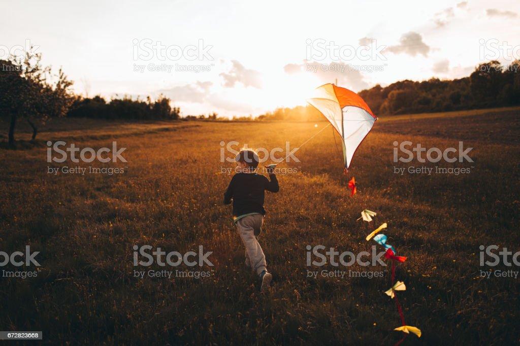 Little boy running a kite - foto stock