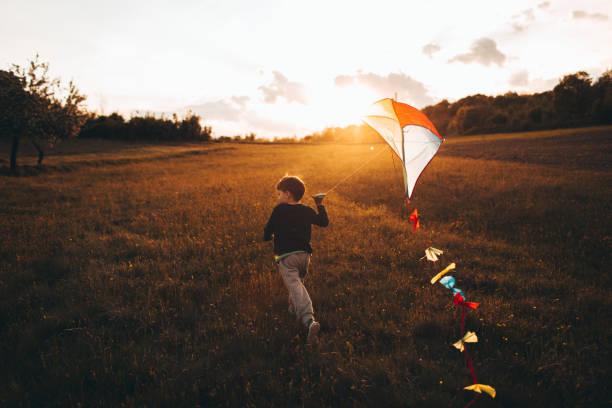 Little boy running a kite stock photo