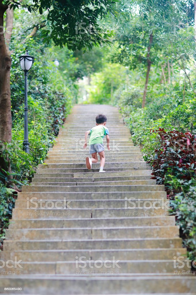 Little boy running in the park stock photo