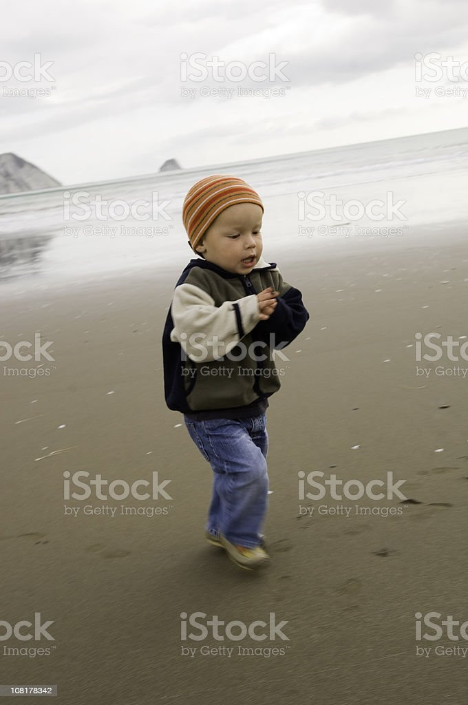 Little Boy Running on Beach During Cold, Cloudy Day royalty-free stock photo
