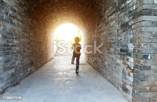 Little boy running through the tunnel.