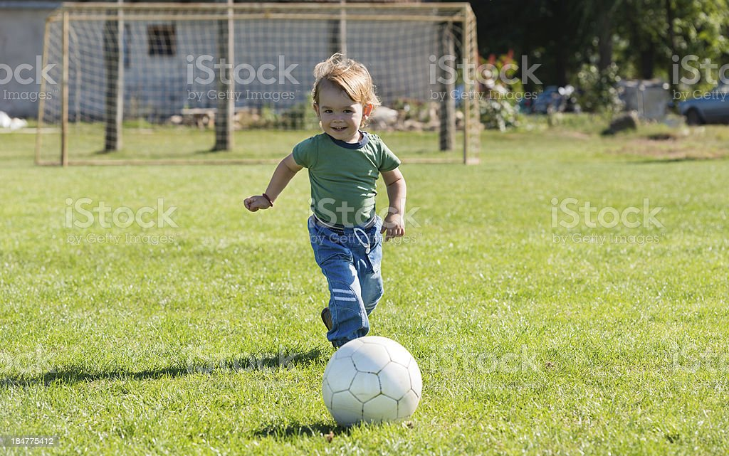 little boy running with ball royalty-free stock photo